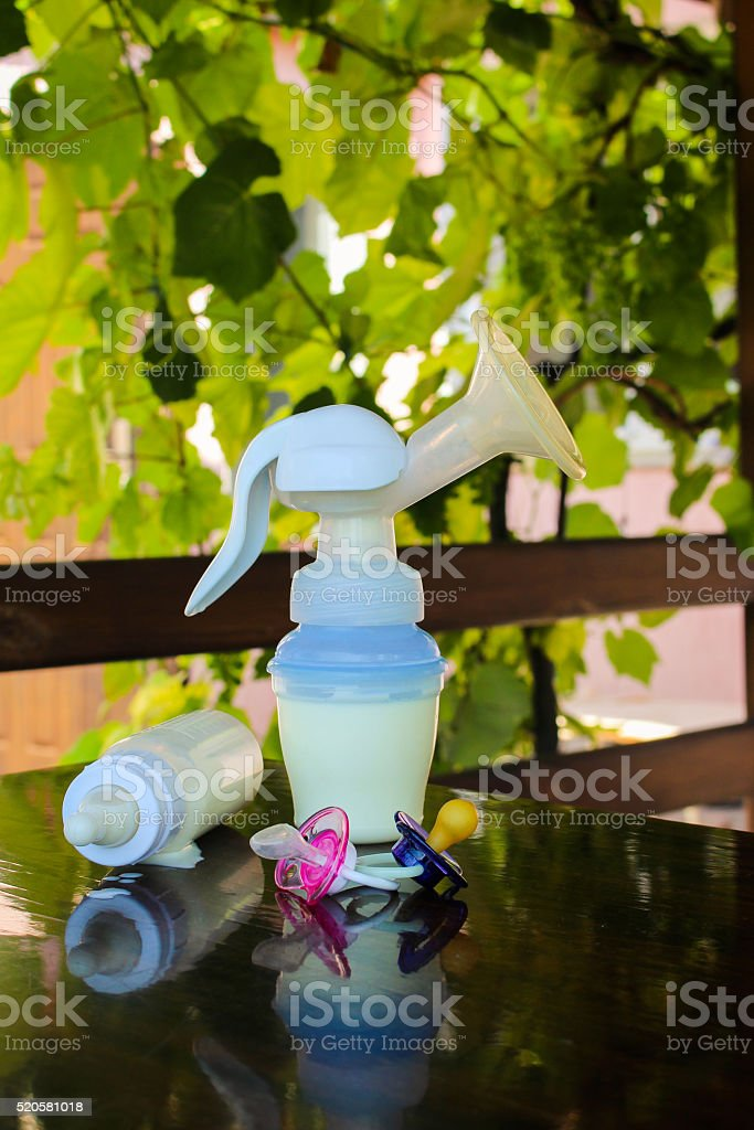 Breast pump, bottle of milk and pacifiers stock photo