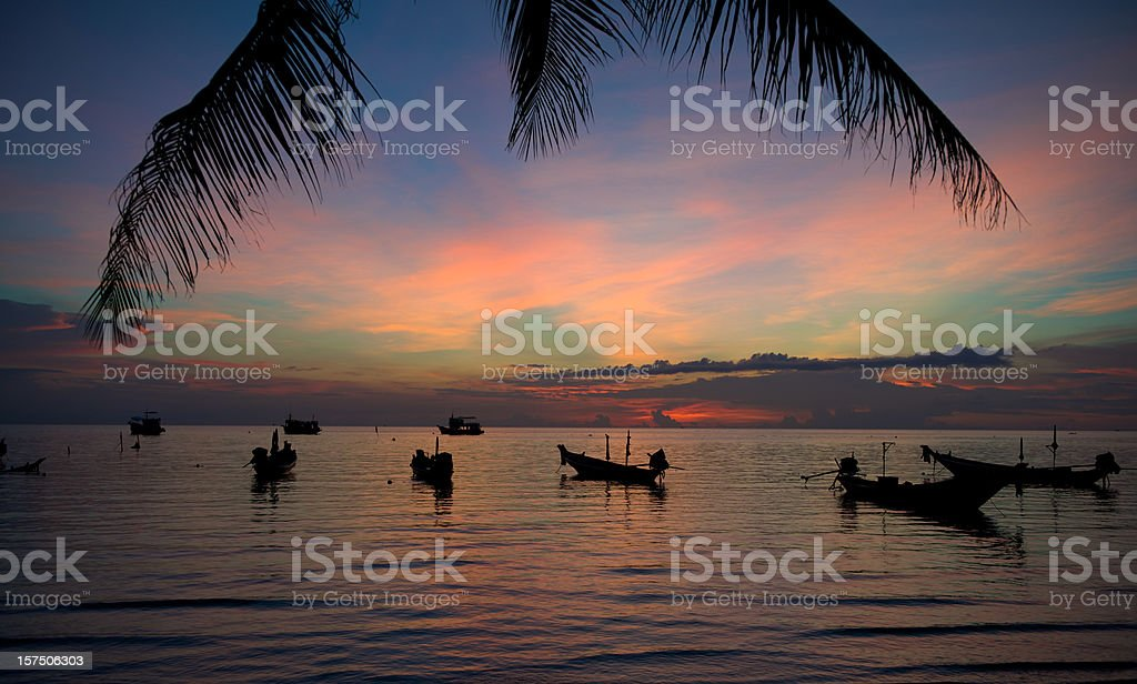 Breathtaking colorful tropical sunset with palm and boat silhouettes (XXXL) royalty-free stock photo