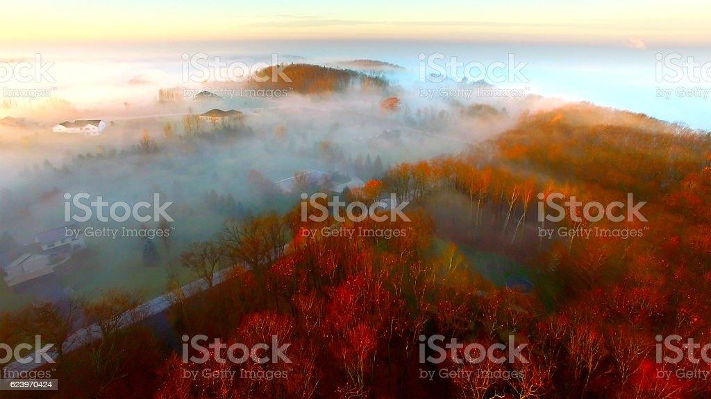 Breathtaking hilltop homes shrouded in Autumn fog at sunrise stock photo