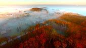 Breathtaking hilltop homes shrouded in Autumn fog at sunrise