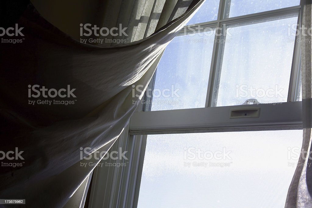 breeze blowing a curtain through an open window stock photo