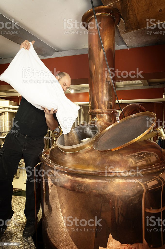 Brewer Adding Malt to a Copper Mash Tun or Kettle stock photo