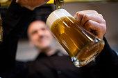 Brewer filling beer in beer glass from beer pump