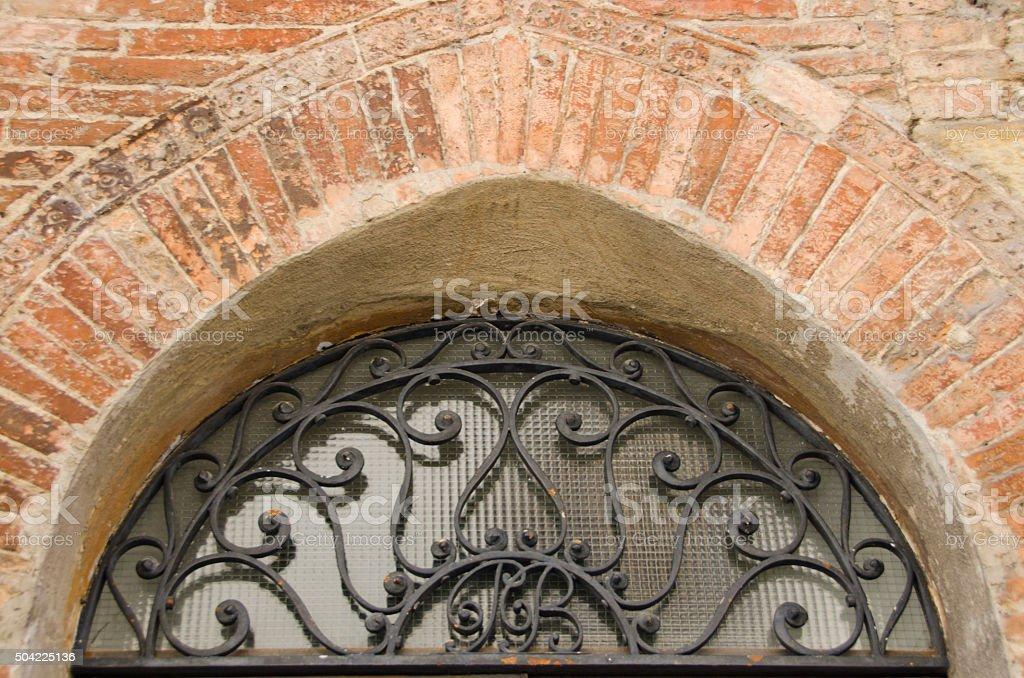 Brick and Iron Above Door in Montepulciano, Italy stock photo