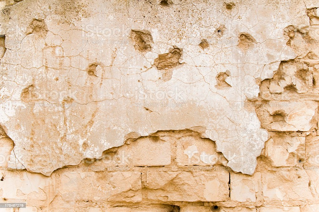 A brick and plastered wall background with bullet holes royalty-free stock photo