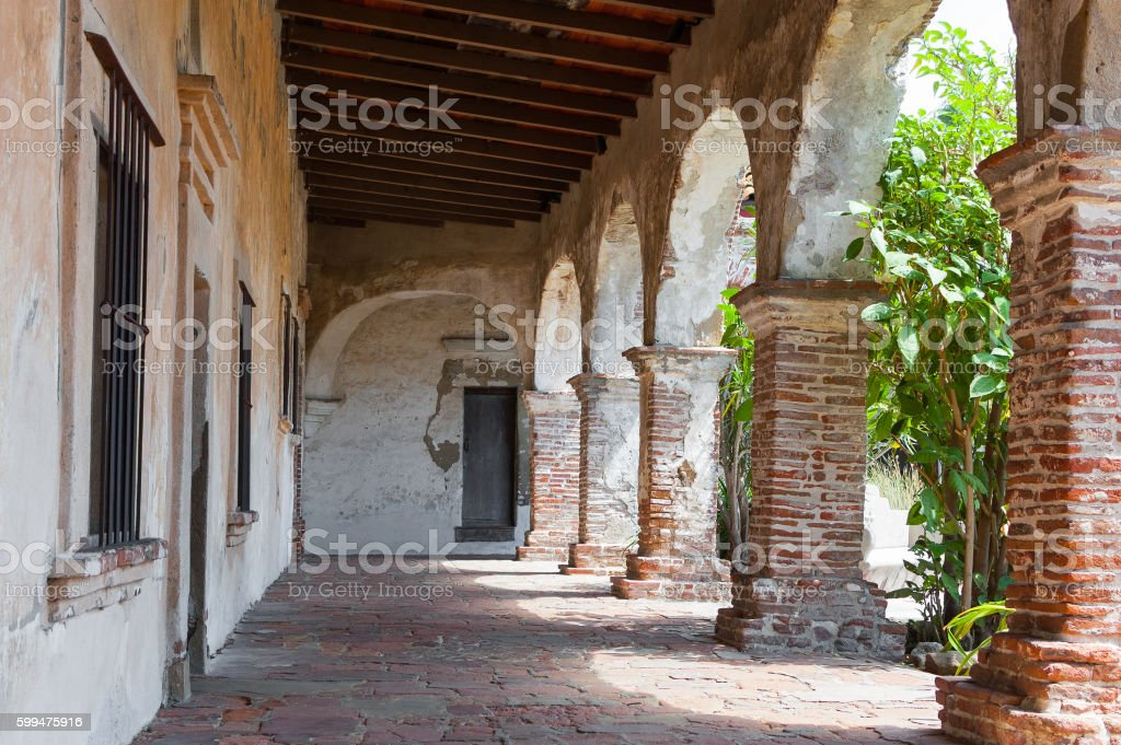 Brick and stone arches line walkway in old Mission ruin stock photo