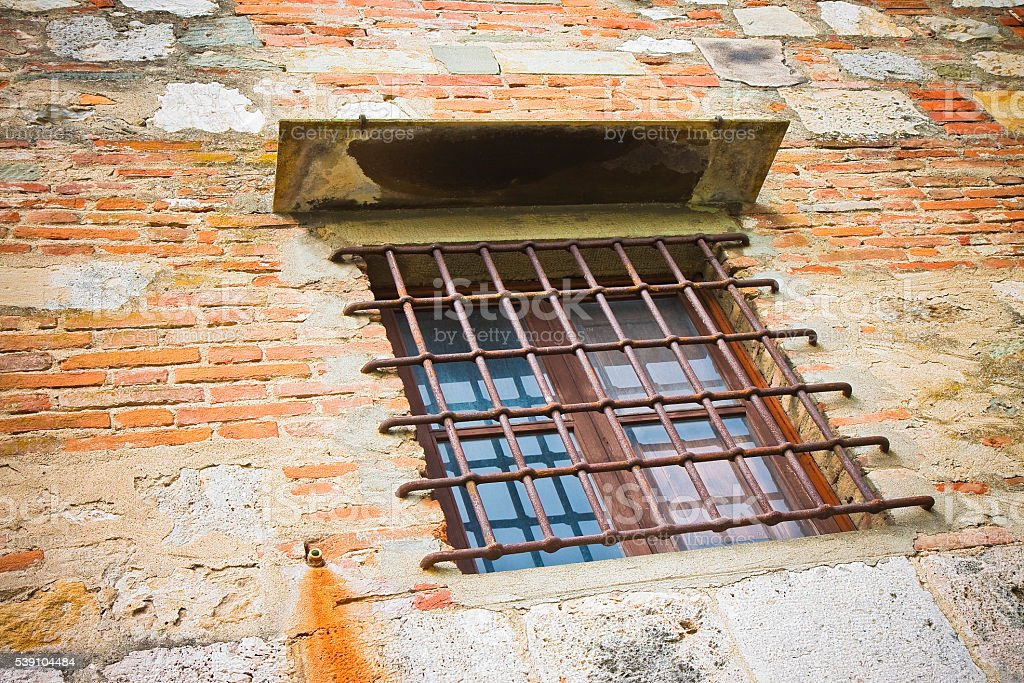 Brick and stone wall with an old wooden window stock photo