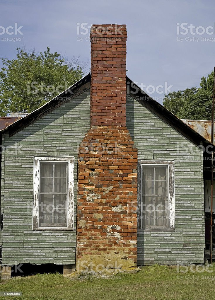 Brick Chimey Between Two Weathered Windows royalty-free stock photo