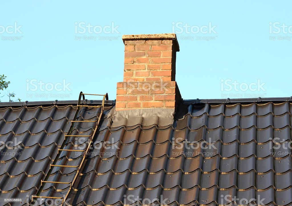 Brick chimney on black roof with metal ladder stock photo