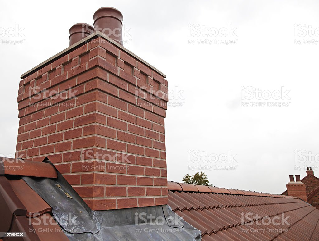 Brick chimney with two chutes sitting atop shingled roof stock photo