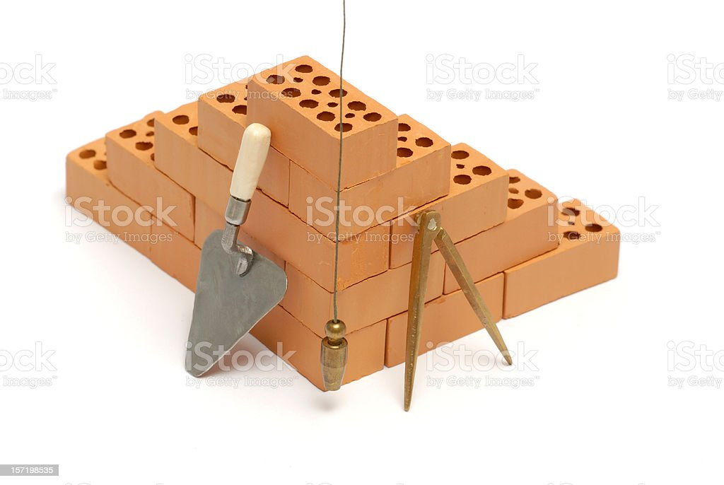 Brick corner with trowel, compass and plumb line stock photo