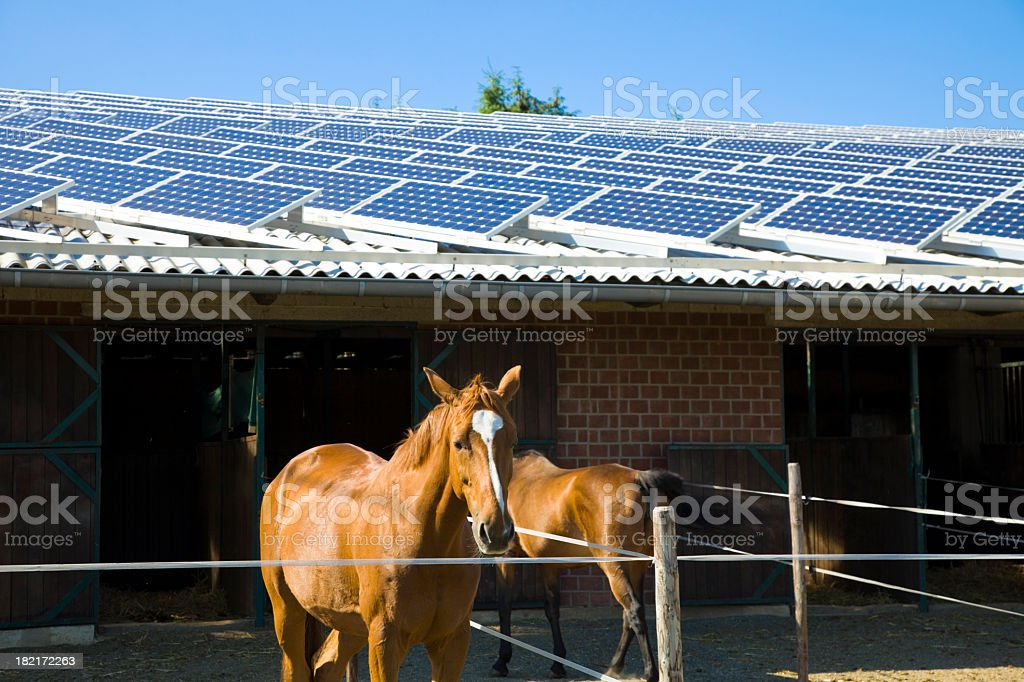 A brick horse stable with a solar paneled roof royalty-free stock photo