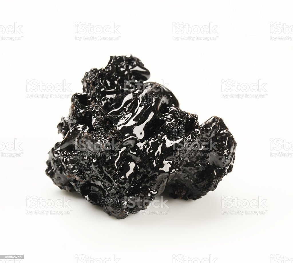 A brick of black tar on a white background stock photo