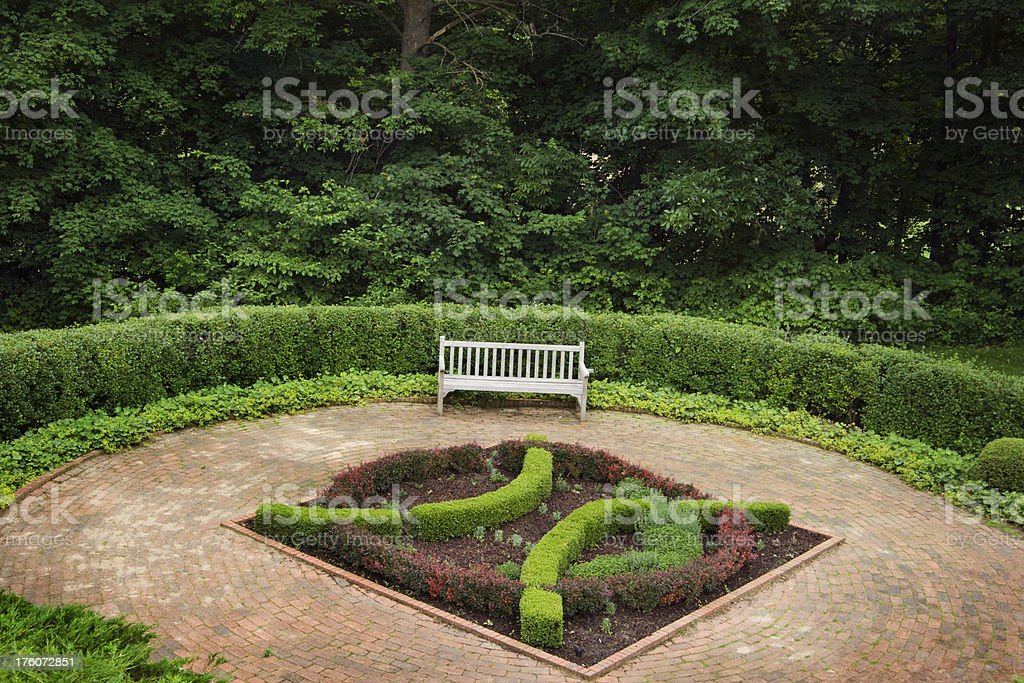 Brick Patio with Garden Bench, Curved Formal Ornamental Hedges, Woods royalty-free stock photo