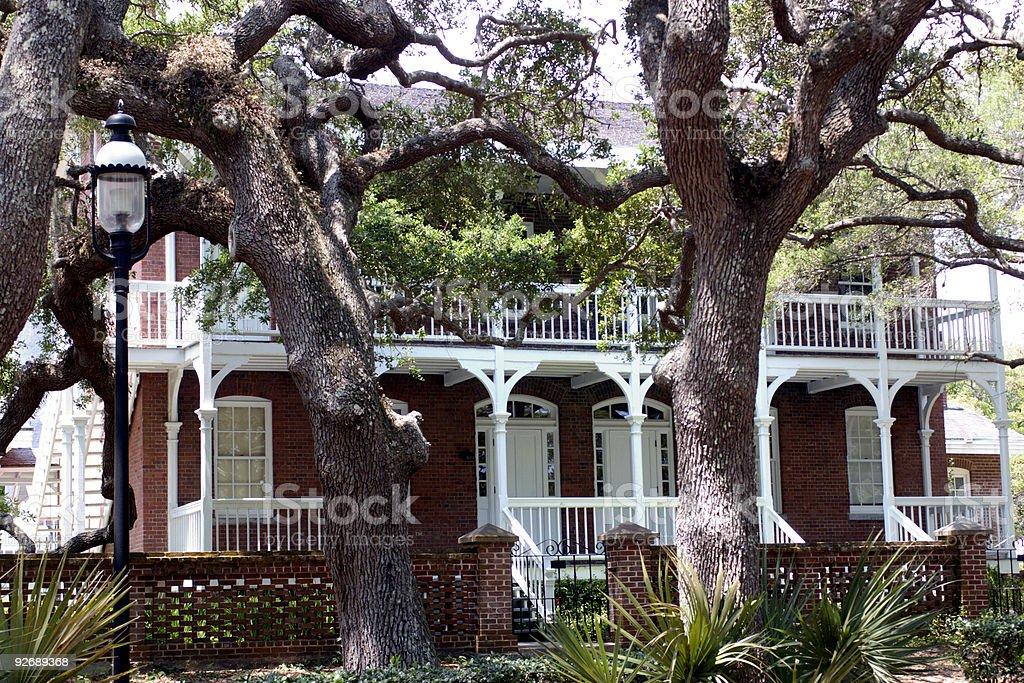 A brick southern mansion with large trees in the front yard stock photo