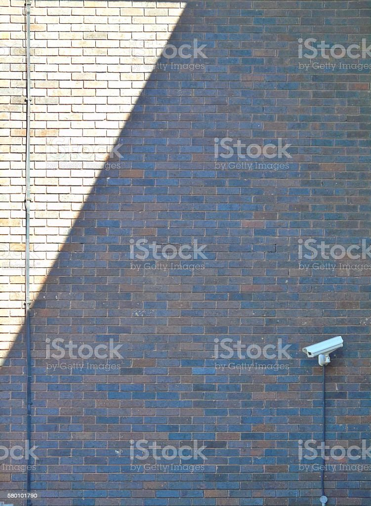 Brick wall and CCTV camera with contrasting light with shadow stock photo