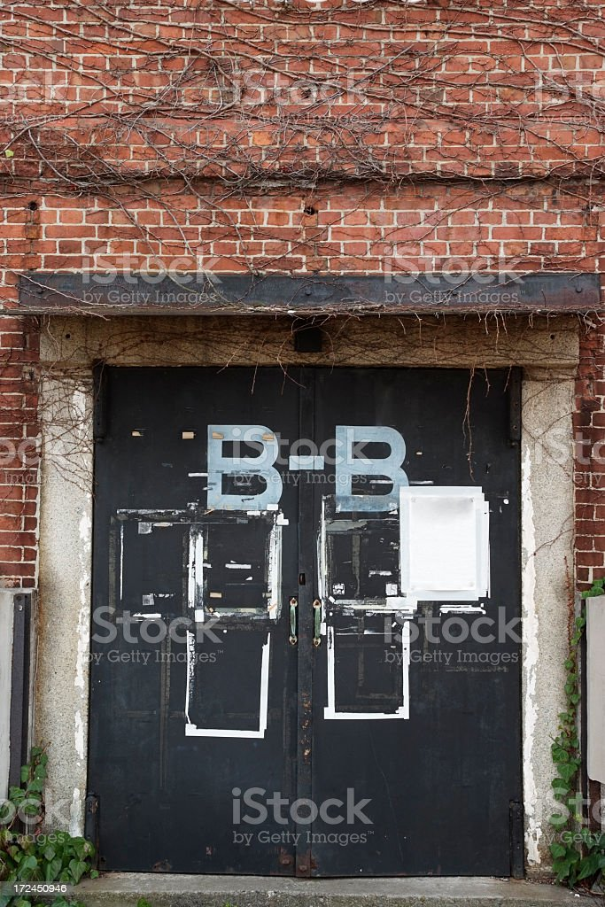 Brick wall and ivy with black door royalty-free stock photo