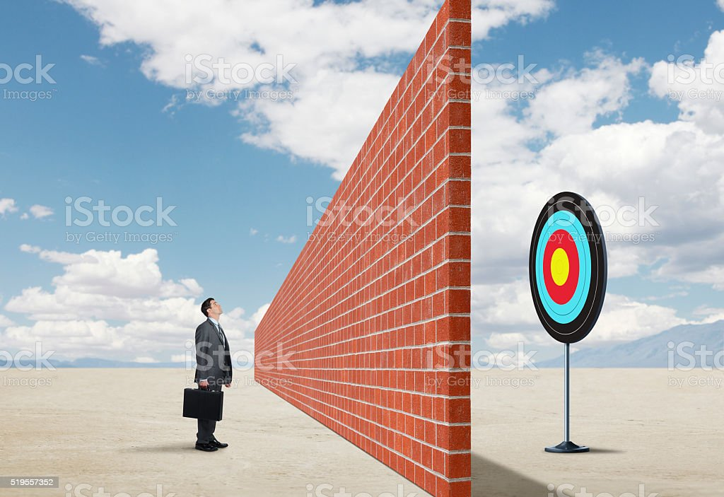 Brick Wall Preventing Businessman From Reaching His Goal stock photo