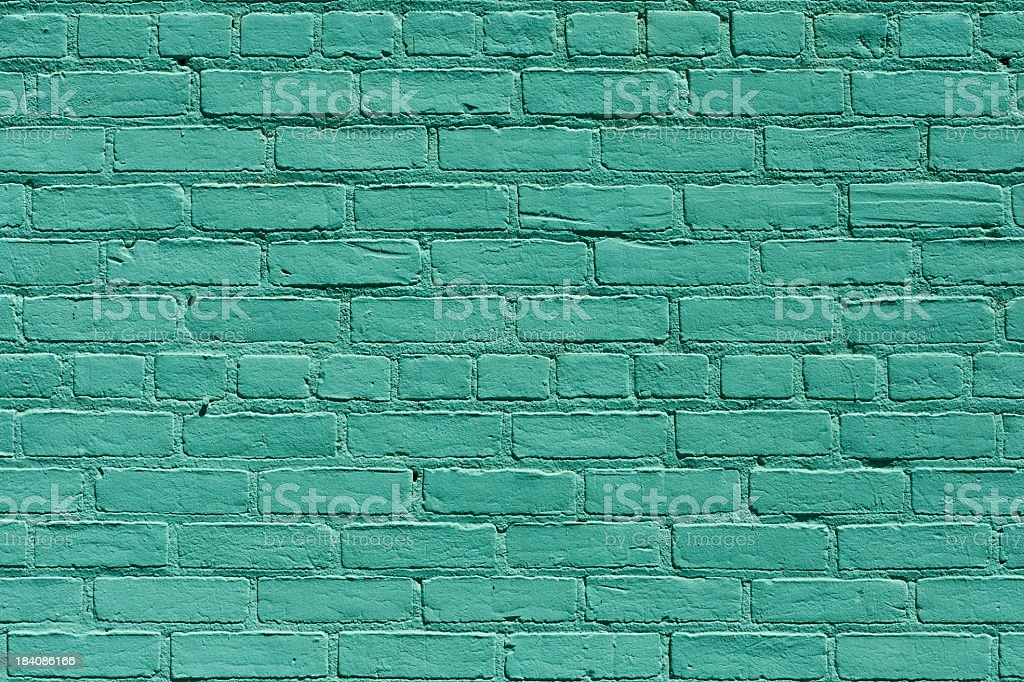 A brick wall that has been painted green royalty-free stock photo