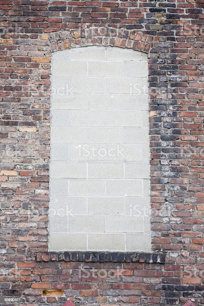 Brick wall with concrete blocks covering window royalty-free stock photo