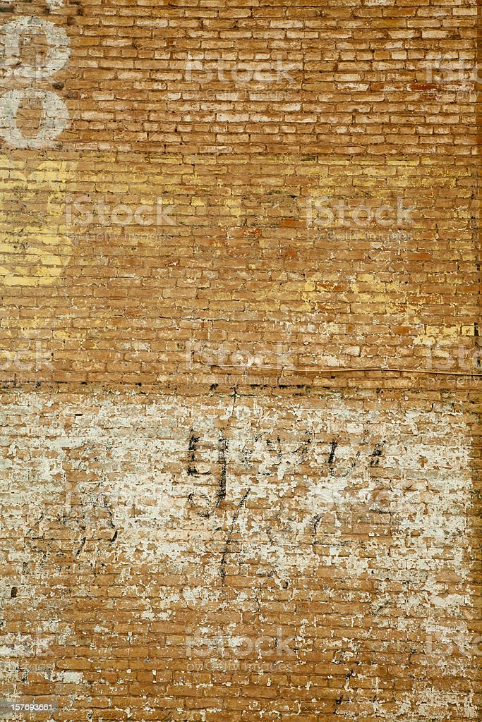 Brick Wall With Fading Painted Signs, Grunge royalty-free stock photo