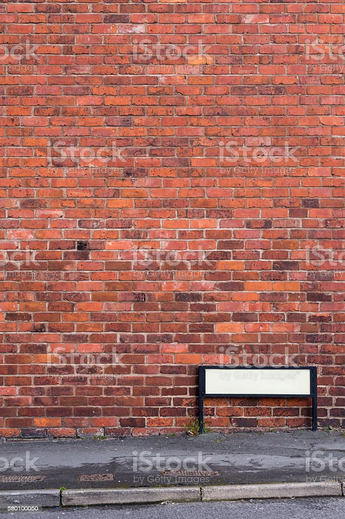 Brick wall with pavement and sign in front stock photo