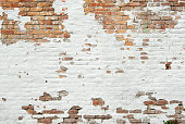 Brick wall with white paint chipping off
