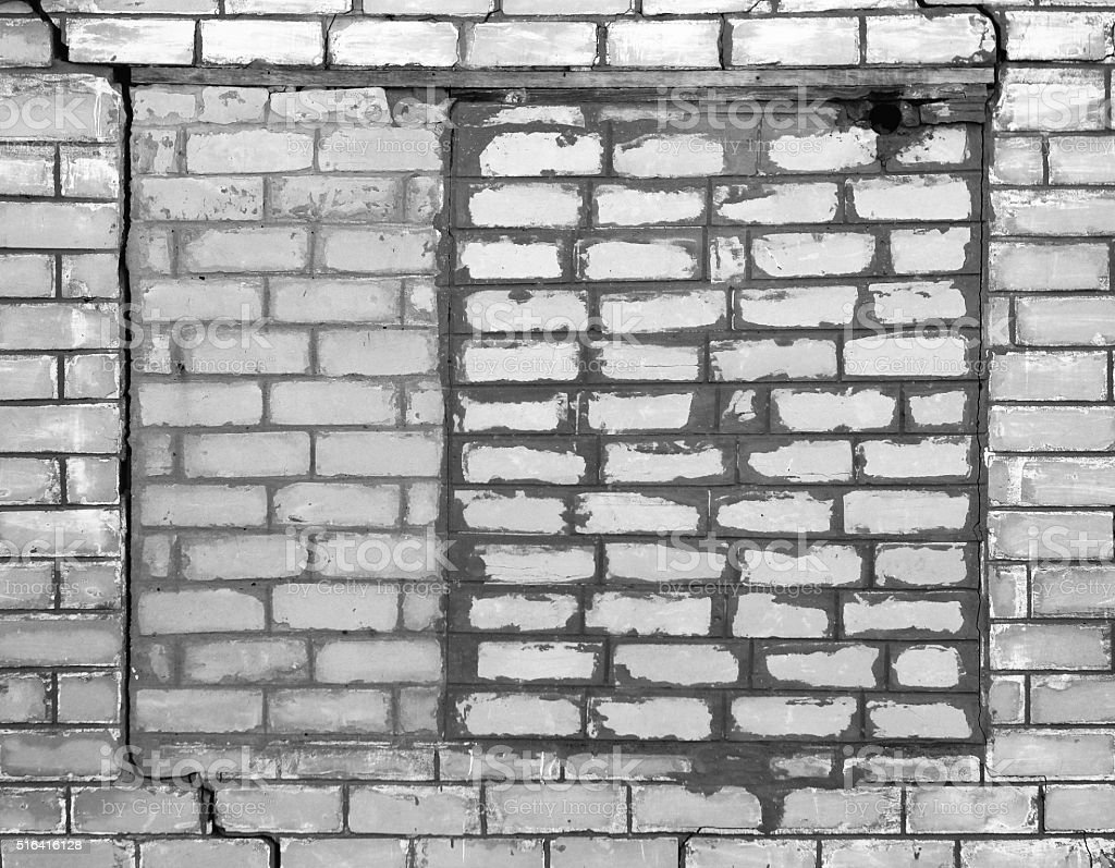 Bricked-up window on the old cracked brick wall stock photo