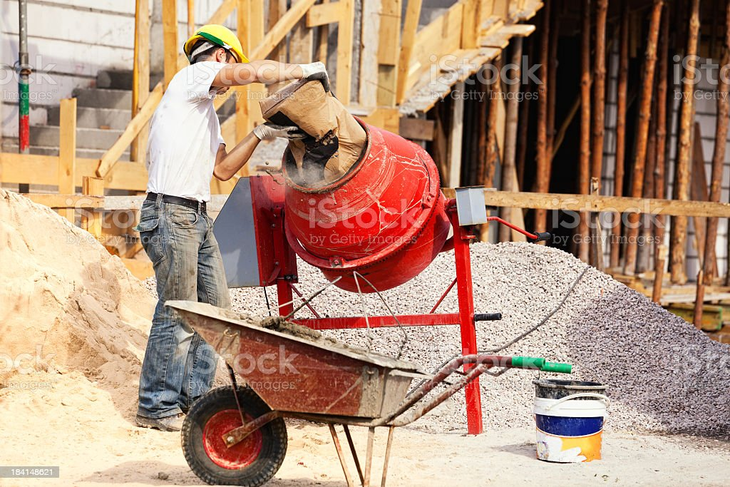 Bricklayer and concrete mixer stock photo