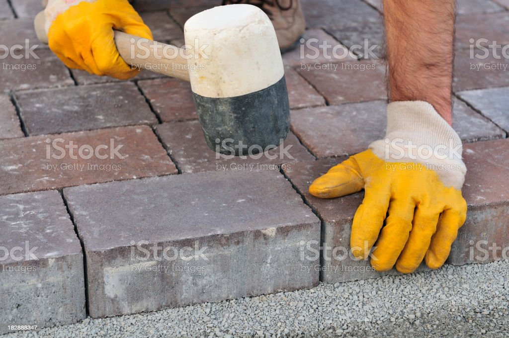Bricklayer arranges cobblestones, close-up, hands in protective gloves, rubber mallet stock photo