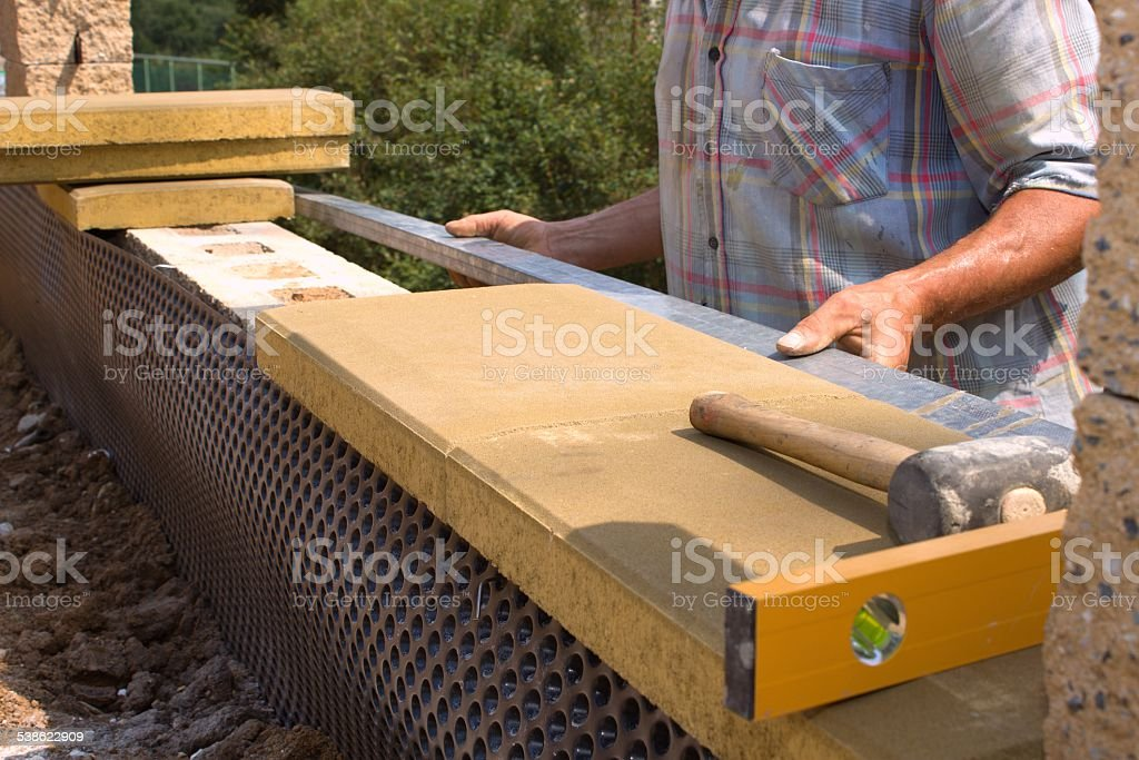 bricklayer builds a wall stock photo