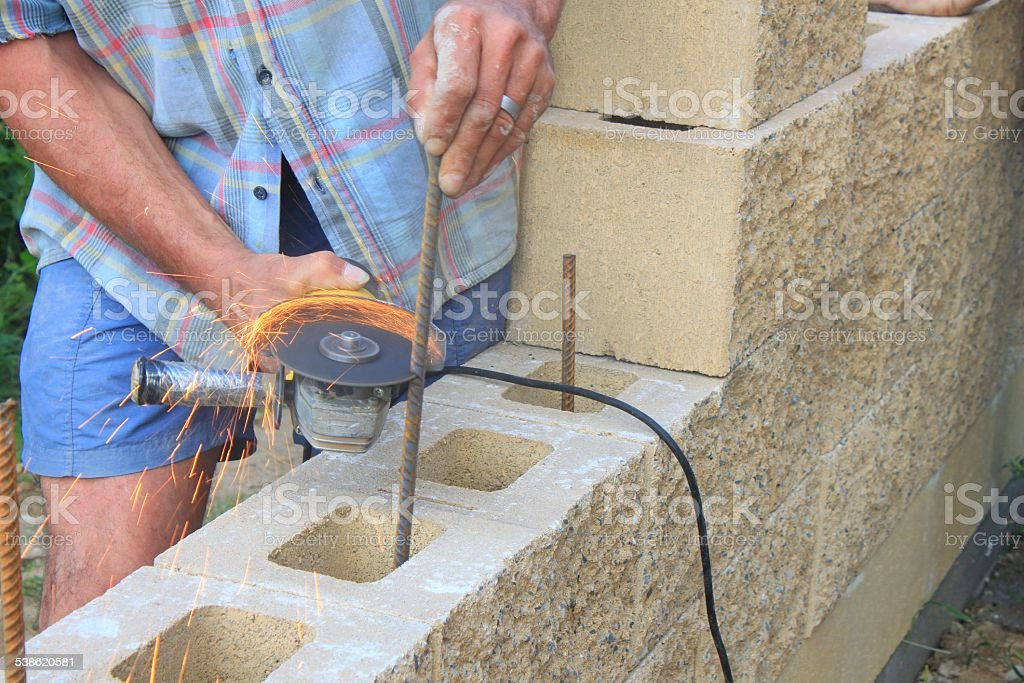 bricklayer builds a wall, rebar cutting angle grinder stock photo