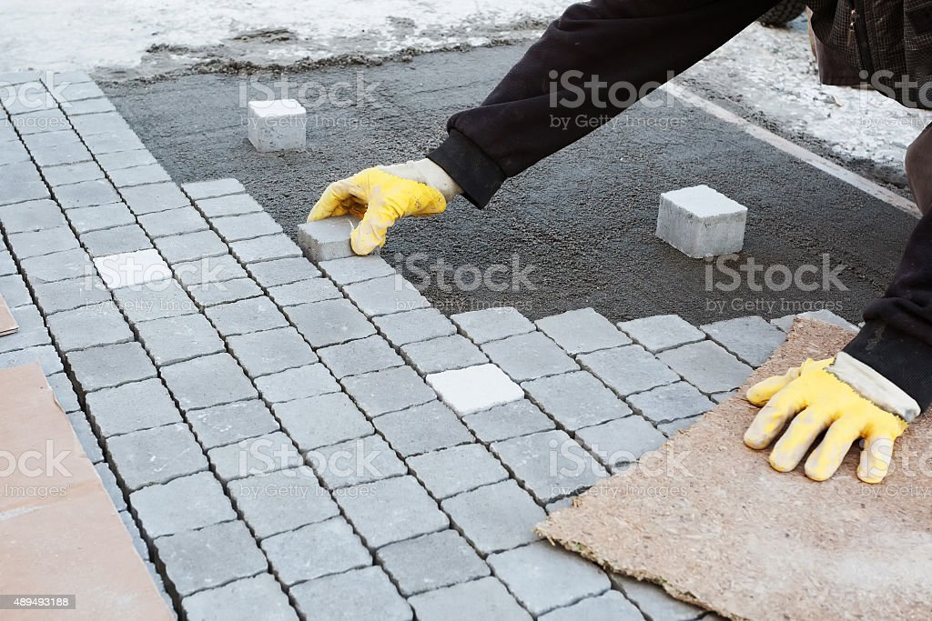 Bricklayer Installing Brick Patio stock photo