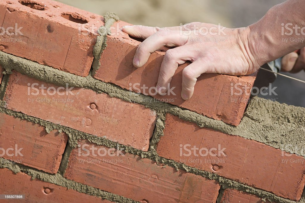 Bricklayer laying red brick into new wall stock photo