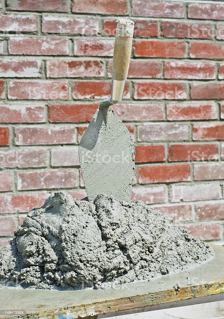 Bricklayer trowel and mud with brick wall stock photo