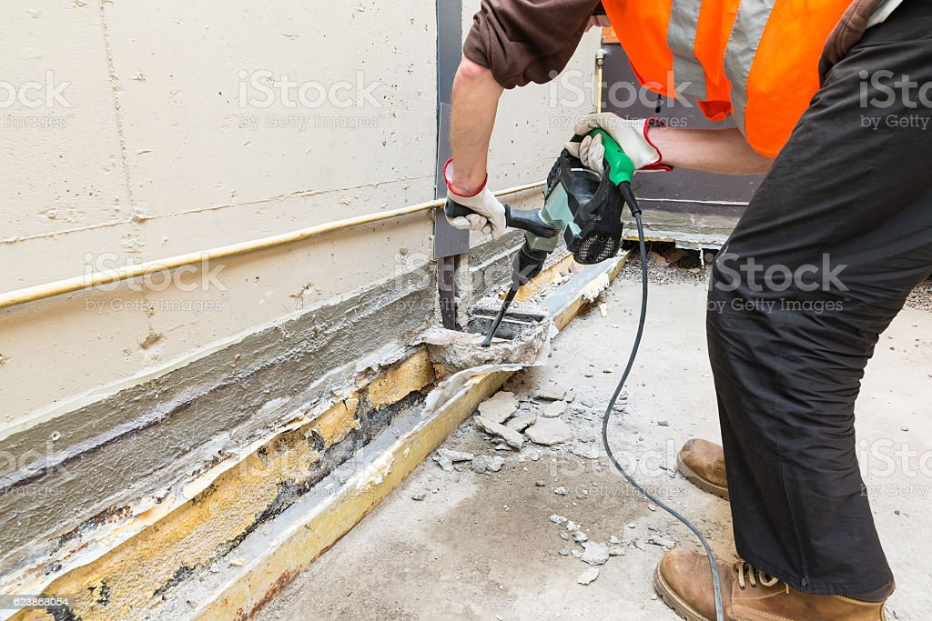 Bricklayer, with professional pneumatic hammer, is demolishing a terrace stock photo