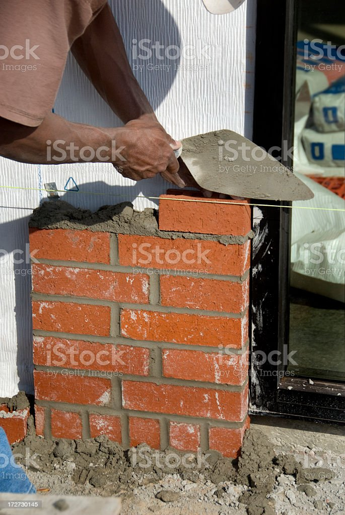 Bricklayer with Trowel Building a Wall royalty-free stock photo