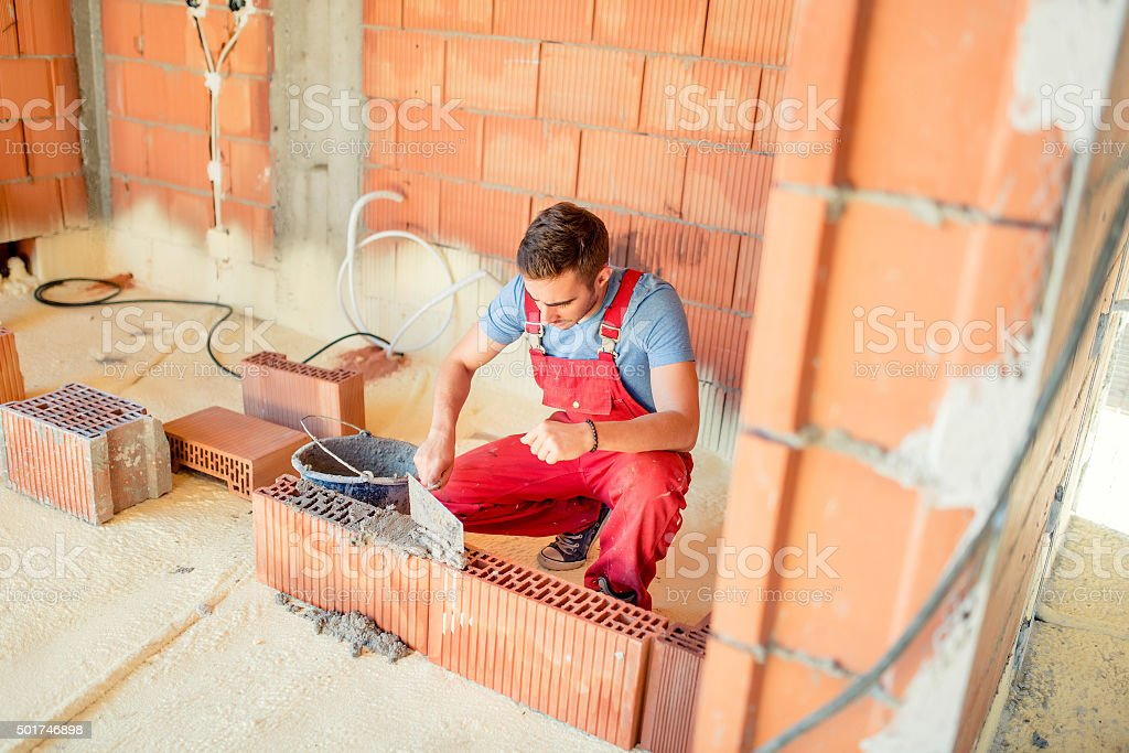 bricklayering with mason on construction site. Industry details stock photo