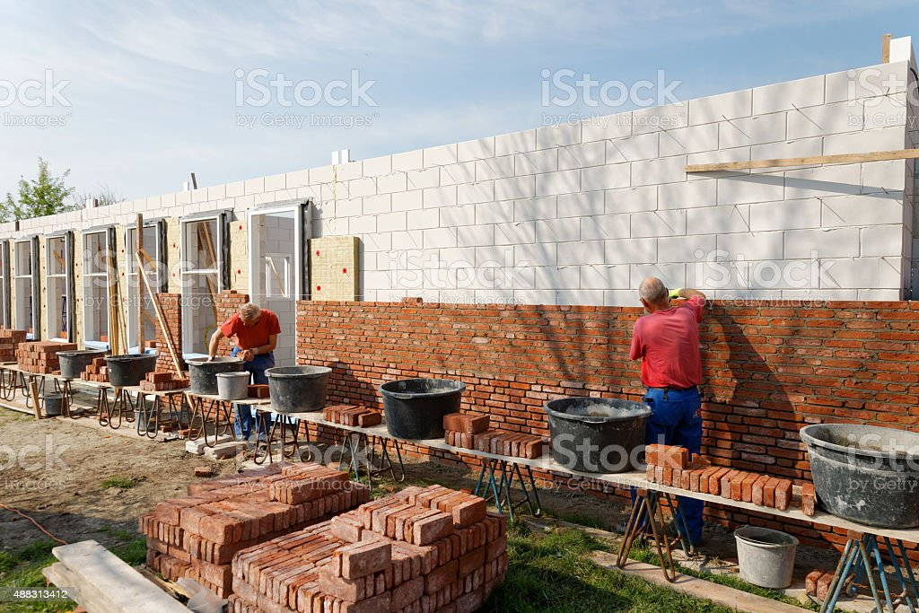 bricklayers building a new house together stock photo