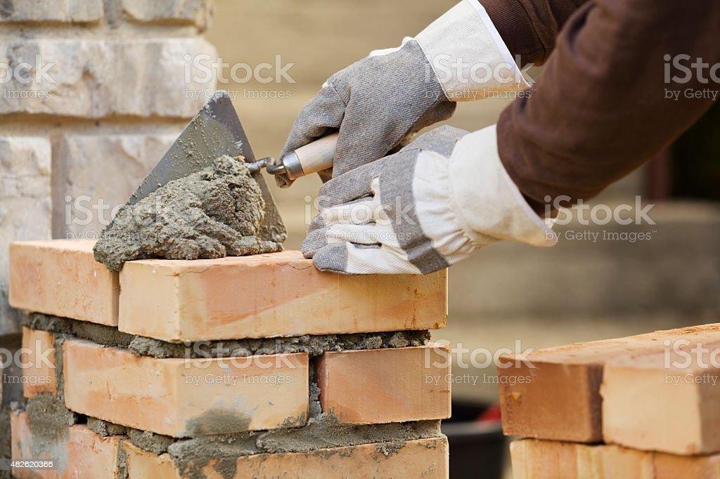 Bricklaying brick wall stock photo