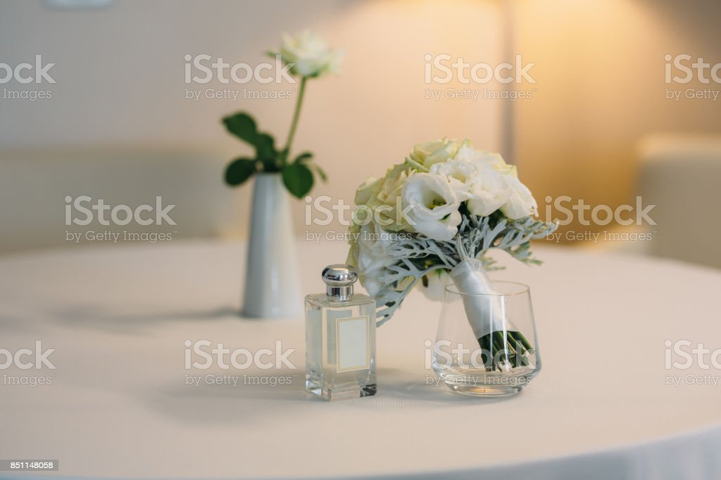 Bridal accessories on a white chair with flowers, perfume shoes....