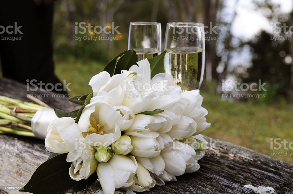 Bridal bouquet in front of two champagne flutes royalty-free stock photo