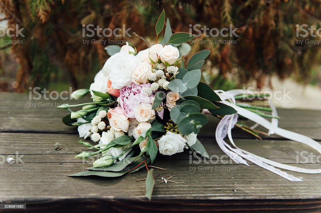 Bridal bouquet of roses on a  wooden planks stock photo