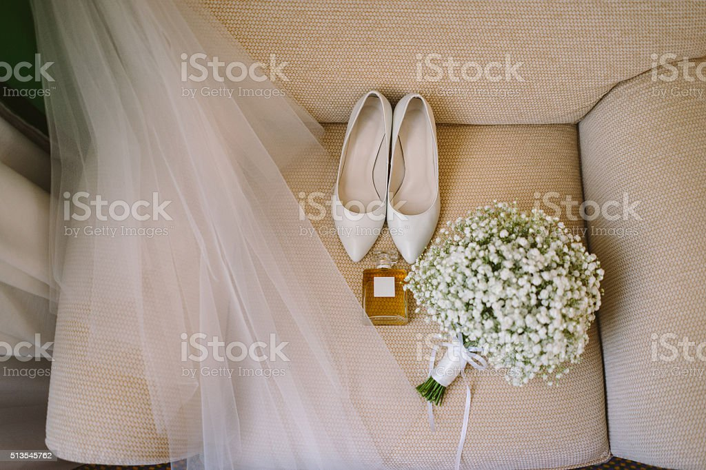bridal bouquet, white shoes, perfume and veil stock photo