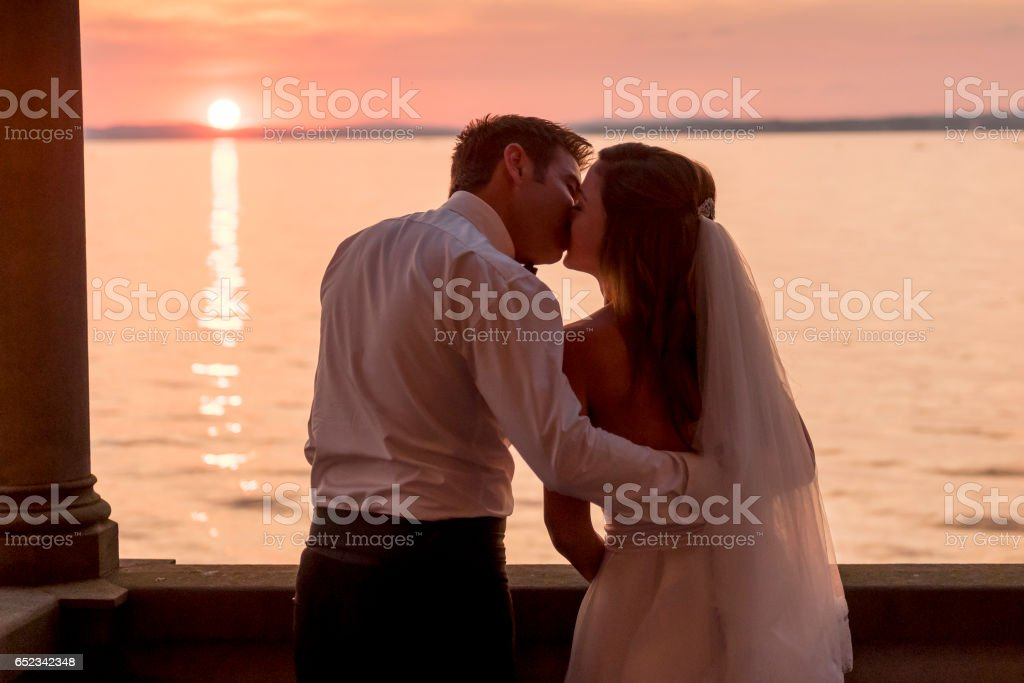 bridal couple kissing on balcony from old villa stock photo