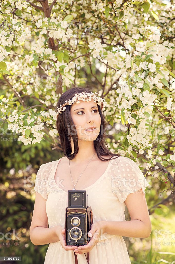 Bridal portrait in a flower crown with old camera stock photo