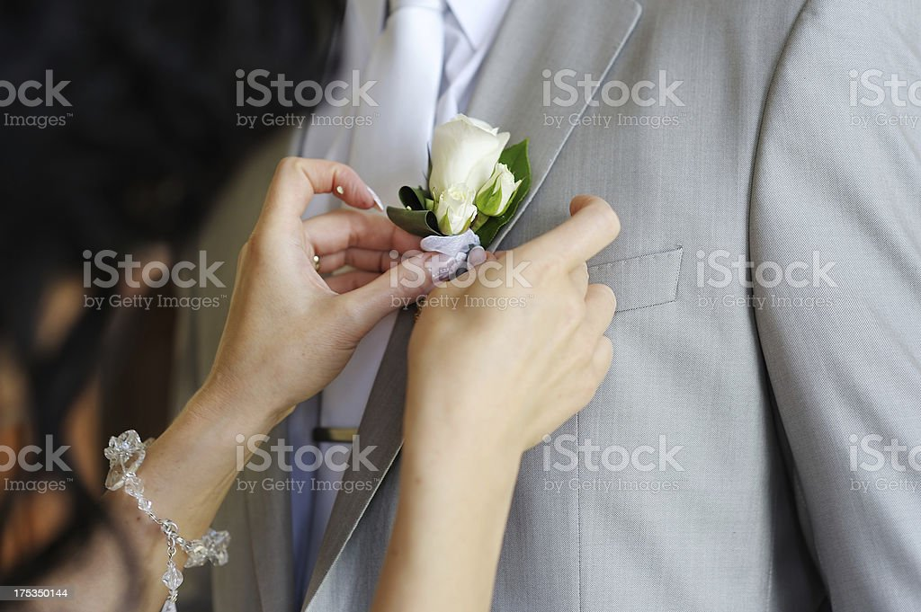 Bride adjusting groom's boutonniere royalty-free stock photo