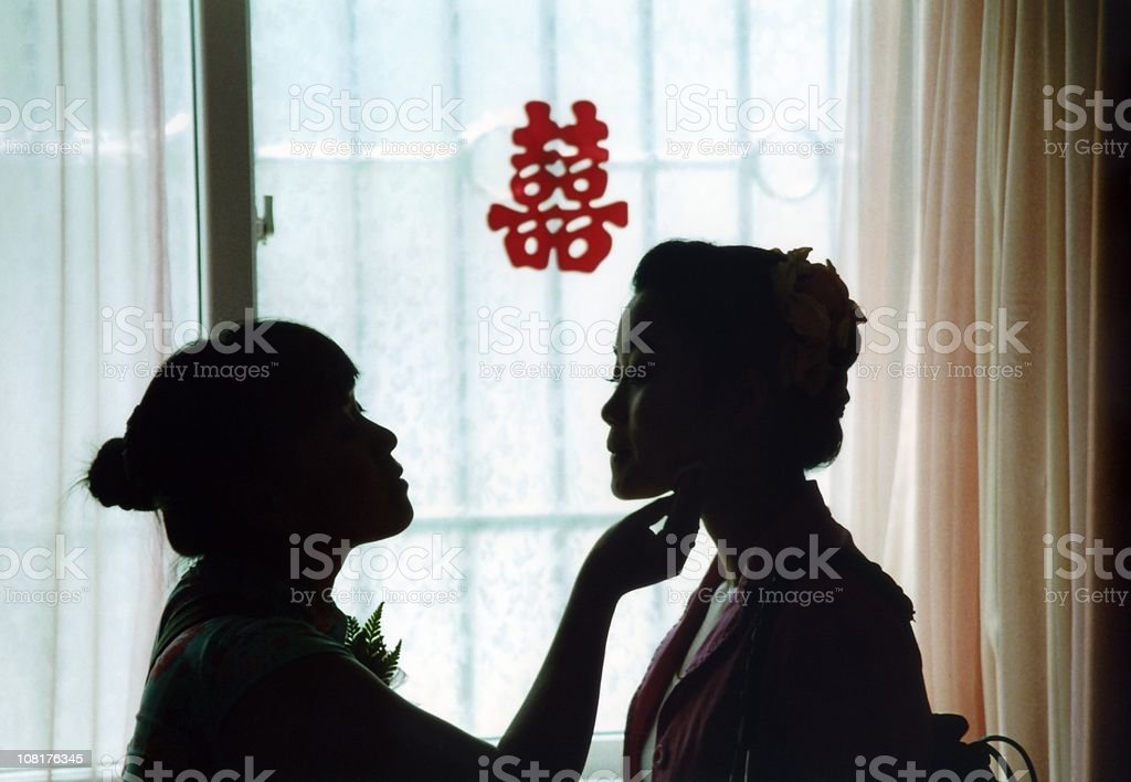 Bride and bridesmaid getting ready for a Chinese wedding. stock photo