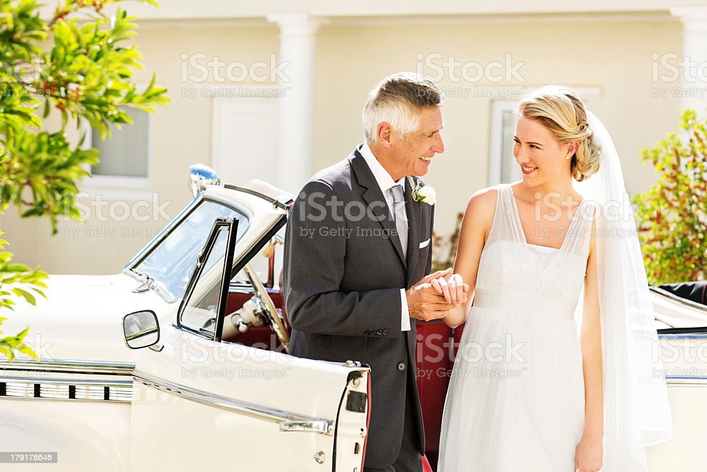 Bride And Father Holding Hands By Car royalty-free stock photo