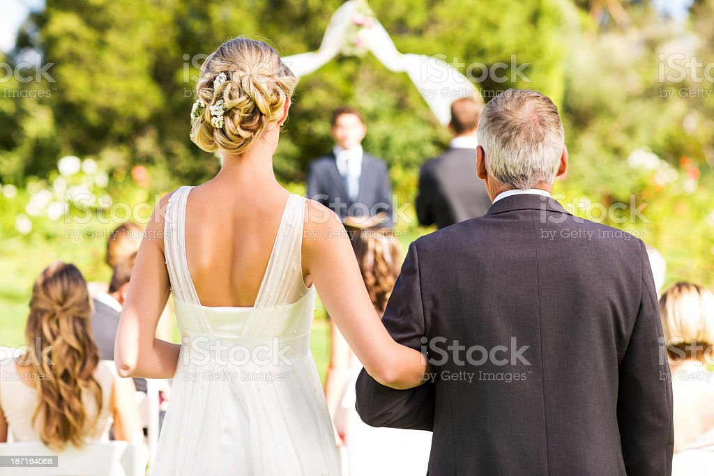 Bride And Father Walking Down The Aisle During Outdoor Wedding stock photo